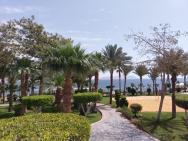 Zahrada plná zeleně a výhled na pláž za ní.